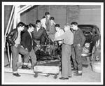 image of a car and mechanics standing around it